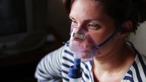 Kobieta jest ubranym maskę dla inhalaci i prowadzi, zbiory