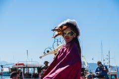 Kobieta jest ubranym maskę paraduje być ubranym karnawałowego kostium w paradzie w Aegina wyspie w Grecja obrazy royalty free