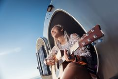 Kobieta jest ubranym masywnego błękita pierścionek bawić się gitarę z białymi dreadlocks fotografia royalty free