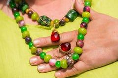 Kobieta jest ubranym piękną gemstone kolię i złotego pierścionek z bursztynem Fotografia Stock