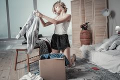 Kobieta jest ubranym piżamy pakuje ubrania ex mąż w pudełka zdjęcie stock