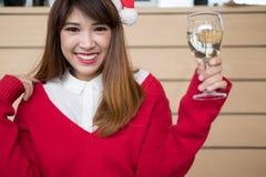 Kobieta jest ubranym Santa Claus kapeluszu & czerwień puloweru mienia wina szkło f Obrazy Stock