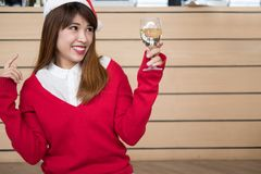 Kobieta jest ubranym Santa Claus kapeluszu & czerwień puloweru mienia wina szkło f Obraz Royalty Free