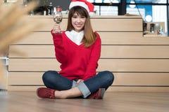 Kobieta jest ubranym Santa Claus kapeluszu & czerwień puloweru mienia wina szkło f Zdjęcia Royalty Free