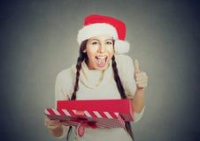 Kobieta jest ubranym Santa Claus otwarcia prezenta kapeluszowego pudełko pokazuje aprobaty Zdjęcia Stock