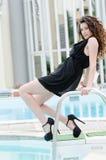 Kobieta jest ubranym suknię i pięty siedzi na basenu pokładu schodkach Obraz Stock