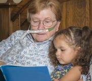 Kobieta jest ubranym tlen czyta dziecko zdjęcia royalty free