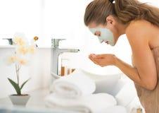 Kobieta jest ubranym twarzową kosmetyk maski domycia twarz Obraz Royalty Free