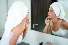 kobieta jest ubranym włosianego ręcznika sprawdza jej skórę Obrazy Stock