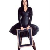 Kobieta jest ubranym w czerni sukni mienia obrazka ramie Zdjęcia Stock