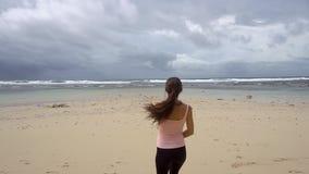 Kobieta jogging morza i podwyżki ręki w powietrzu cieszy się wolność na plaży przy wschodem słońca zbiory wideo