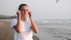 Kobieta jogging na dennej plaży i stawia słuchawki słuchać muzykę zbiory wideo