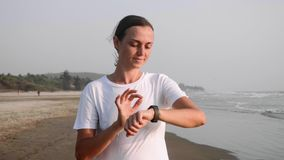 Kobieta jogging na oceanie plażowym i używa sprawność fizyczna zegarka zegar zdjęcie wideo