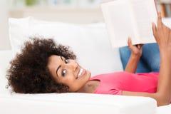 Kobieta kłaść na ona z powrotem, trzymający otwartą książkę obraz stock
