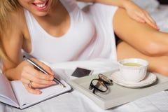 Kobieta kłaść w łóżku i pisze jej notatniku obraz stock