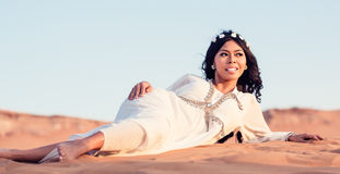 Kobieta kłaść w piasku Arabska pustynia Fotografia Stock