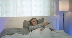 Kobieta kłama na łóżku w sypialni i ogląda TV zbiory