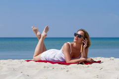 Kobieta kłaść na piasku blisko dennego mówienia telefonem Fotografia Stock