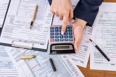 Kobieta kalkuluje jej podatki, 1040 indywidualnych podatków form fotografia royalty free
