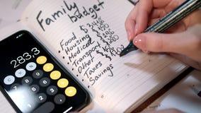 Kobieta kalkuluje rodzinnego budżet na kalkulatorze i writing w notatniku zdjęcie wideo
