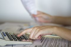 Kobieta kalkuluje wartość kwity dla podatkowego zamierza obrazy stock