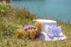 Kobieta kapelusz z kwiatami na trawie Obrazy Royalty Free