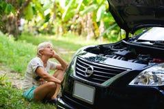 Kobieta kierowca na lasowej drogi czekania pomocy obraz stock