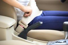 Kobieta kierowcy klamra w górę pasa bezpieczeństwa w samochodzie Obrazy Stock