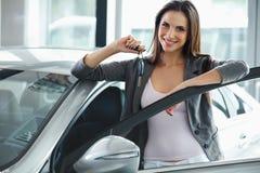 Kobieta kierowcy mienia samochodu klucze Samochodowa sala wystawowa Zdjęcia Royalty Free