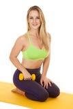 Kobieta klęczy zielony sporta stanika chwyta ciężar Fotografia Stock