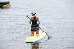 Kobieta klęczy na paddleboard w zalewisku Zdjęcia Stock