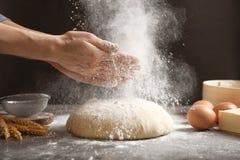 Kobieta klascze ręki i tryskaczową mąkę zdjęcia royalty free