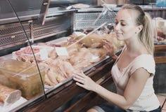 Kobieta klient kupuje świeżego kurczaka rozdziela w mięsnym sklepie obrazy royalty free