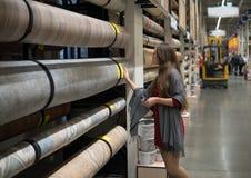 Kobieta klient wybiera linoleum podłoga w hypermarket zdjęcia stock