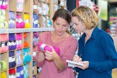 Kobieta klient wybiera różnorodną przędzę w szwalnym sklepie fotografia royalty free