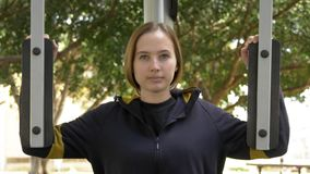 Kobieta kończy jej ćwiczenia używać ulicznego trenera zbiory