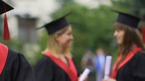 Kobieta kończy studia uczni opowiada, dyskutujący plan na przyszłość, trzyma dyplomy zbiory