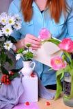 Kobieta komponuje bukiet, stawia kartę w kopertę i tulipany i chryzantemy fotografia stock