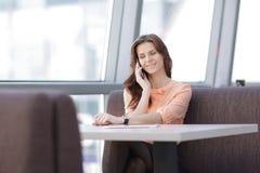 Kobieta konsultant z smartphone obsiadaniem przy jej biurkiem w biurze fotografia royalty free
