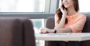 Kobieta konsultant z smartphone obsiadaniem przy jej biurkiem w biurze obraz royalty free