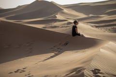 Kobieta kontempluje w piasek diunach podczas zmierzchu zdjęcie stock