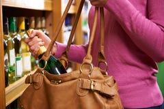 Kobieta Kraść butelkę wino Od supermarketa Zdjęcia Stock