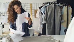 Kobieta krawczyna jest tocznym tkaniny ryglem na studio stole wtedy bierze szata rysunek na papierze i nakreślenie out projekty zdjęcie wideo