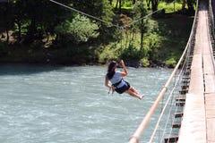 Kobieta krzyżuje rzekę z tyrolean trawersowaniem zdjęcie stock