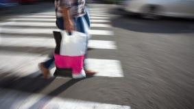Kobieta krzyżuje ulicę z torba na zakupy Fotografia Royalty Free