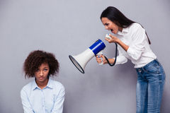 Kobieta krzyczy przez loudspaker na jej przyjacielu Obrazy Royalty Free