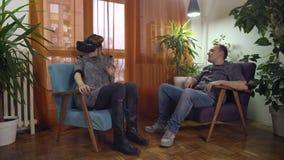 Kobieta krzywdzi szyję podczas gdy używać rzeczywistość wirtualna gogle gniewnych na mężczyźnie zbiory