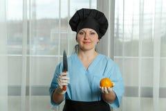 Kobieta kucharz trzyma pomarańcze w jej ręce na innej ręce i, nóż Obrazy Stock