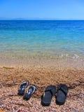 Kobieta kuje mężczyzna ` s buty na plaży obraz royalty free