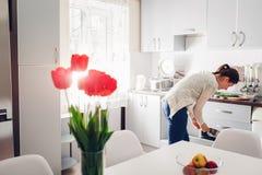 Kobieta kulinarny gość restauracji w kuchni Młoda dziewczyna bierze nieckę nowoczesna kuchnia projektu Obrazy Royalty Free